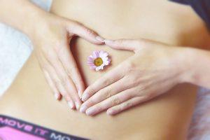 mujer con una flor en el abdomen