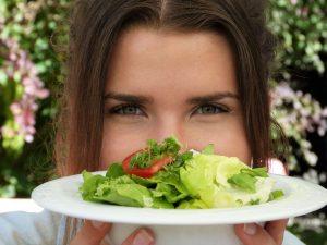 mujer comiendo ensalada de hojas verdes con la clorofila