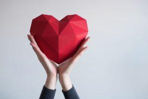 manos con un corazón de papel