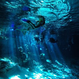 mujer nadando, vista debajo del agua, experiencia de ecoturismo