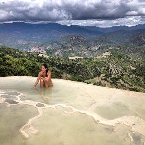 mujer sentada en el piso con vista hacia la montaña